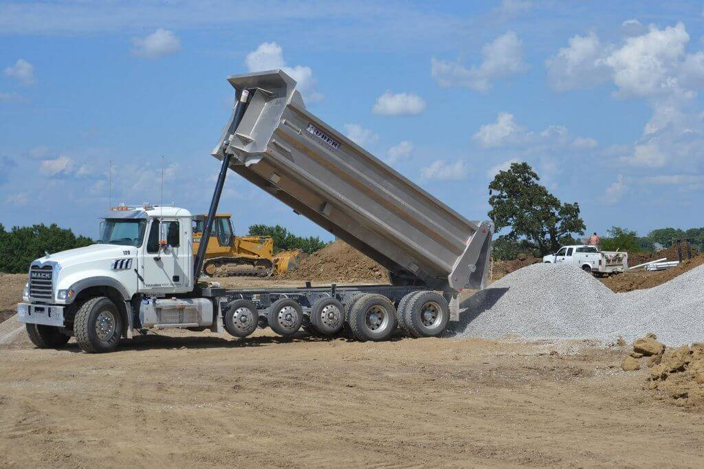 A Huber Hauling tri-axle truck dumps material.